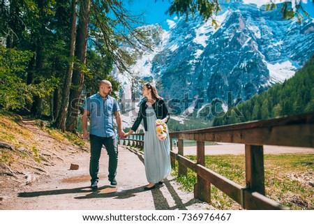 Young Couple against lake, summer park. lago di braies,Dolomite,Italy. Man and woman on vacation in beautiful place. #736976467