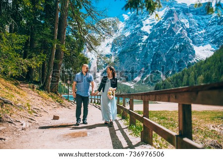 Young Couple against lake, summer park. lago di braies,Dolomite,Italy. Man and woman on vacation in beautiful place. #736976506