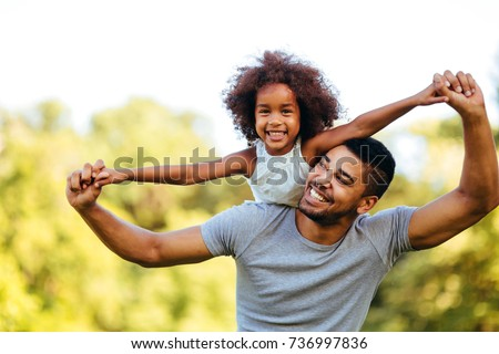 Portrait of young father carrying his daughter on his back #736997836