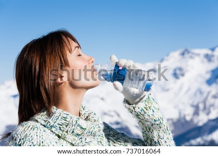 woman drinking mineral water in snow #737016064