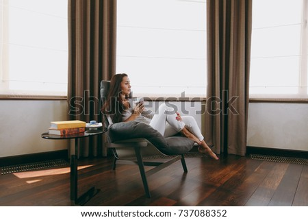 The beautiful young woman at home sitting on modern chair in front of window, relaxing in her living room and drinking coffee or tea #737088352