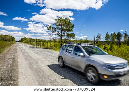 Road, the natural landscape and blue sky with clouds. A passing all terrain vehicle. Lonely tree near the road. #737089324