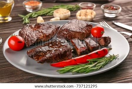 Plate with yummy grilled steaks on wooden table #737121295