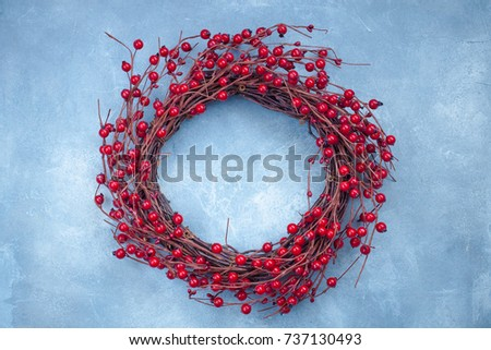 Christmas wreath with red berries on the light blue background #737130493