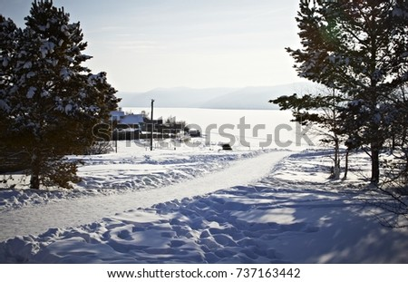 Winter view from the mountain to the wide Siberian river and a huge frozen lake #737163442