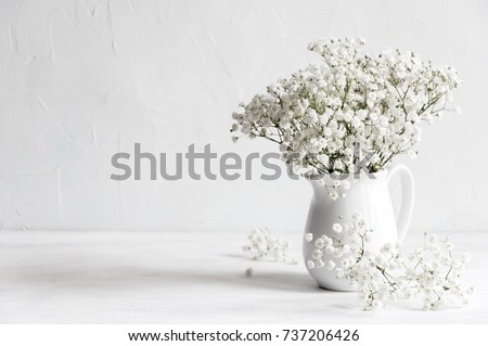 Soft home decor, white jug, vase with white small flowers on a white vintage wall background and on a wooden shelf. Interior. #737206426