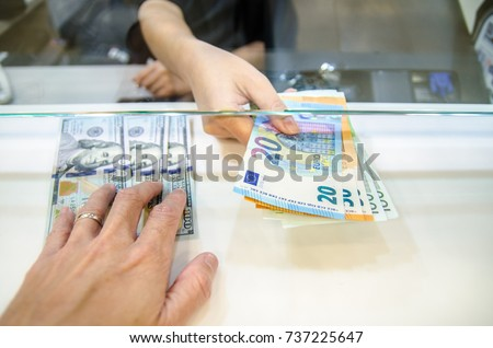 Exchange money, Exchange US dollar or American dollars (USD) for EUR money, A man and women are exchanging dollars for euros. Royalty-Free Stock Photo #737225647