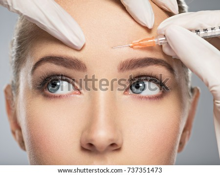 Portrait of young Caucasian woman getting cosmetic injection of botox in forehead. Beautiful woman gets botox injection in her face. #737351473