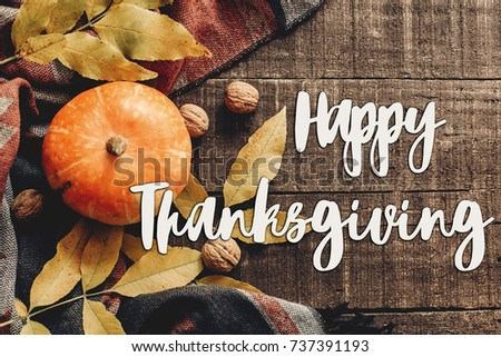 happy thanksgiving text sign  flat lay. pumpkin with leaves and walnuts on stylish scarf top view, space for text. seasonal greetings, autumn fall holidays. harvest time. cozy mood #737391193