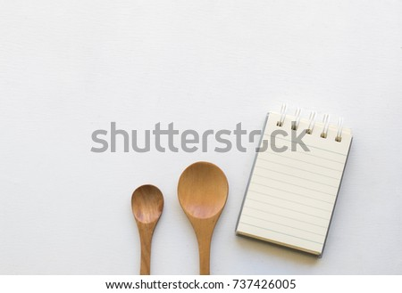 Notepad with spoons and vegetable on wood wood background.Using wallpaper for food, kitchen and cook composition image Take note product for book with paper and concept or copy space with note