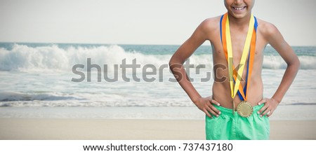 Cheerful swimmer boy wearing medals against two starfish kept on sand #737437180