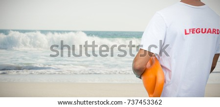 Mid section of male lifeguard with rescue buoy against two starfish kept on sand #737453362
