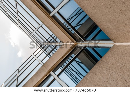 Abstract image of glass and concrete building. Architectural exterior facade and detail. Abstract color background. Modern architecture and design. #737466070