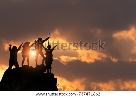 Businessman and women group hike on the peak of silhouette rocks mountain at sunset, success, winner and leader concept . #737471662