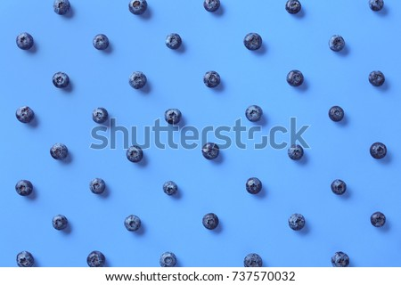 Colorful pattern of blueberries on blue background. From top view