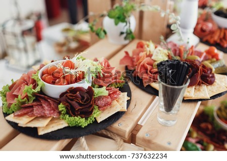 Black dishes with sliced meat and cheese #737632234