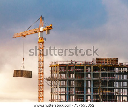 Construction of a high-rise building with a crane. Building construction using formwork. The construction crane and the building against the blue sky. Royalty-Free Stock Photo #737653852