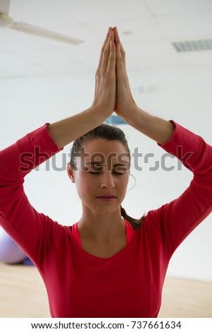 Young woman meditating while doing tree pose in yoga studio #737661634