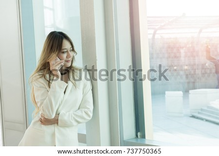 Beautiful women use the phone at the window. #737750365