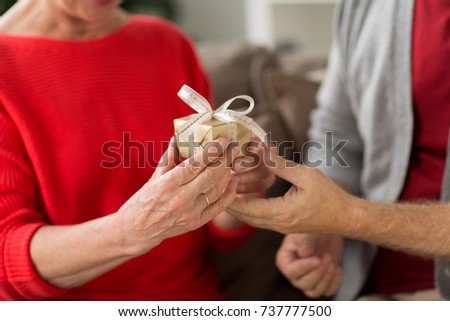 christmas, holidays and people concept - close up of senior couple with gift box at home #737777500
