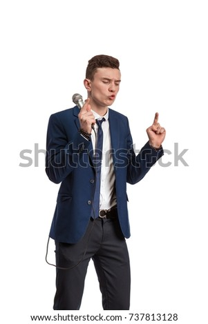 A young man in a blue suit is holding a microphone, singing and posing against a white background #737813128