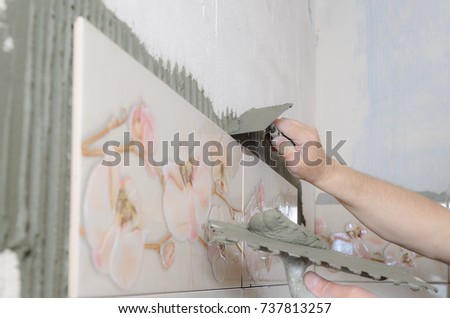 Tilers hands are putting on a tile adhesive on the wall in the bathroom. #737813257