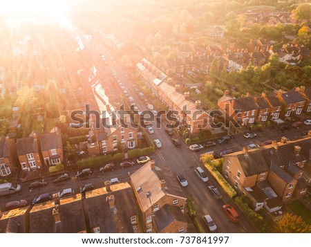 Sun setting over a traditional British neighbourhood. Lens flare and warm colours to give a homely effect. Royalty-Free Stock Photo #737841997