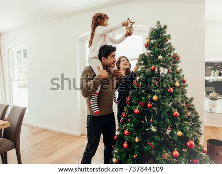 Family decorating a Christmas tree. Young man with his daughter on his shoulders helping her decorate the Christmas tree. #737844109