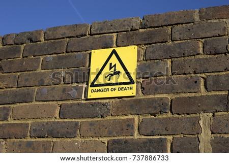 death of danger board on brick wall #737886733