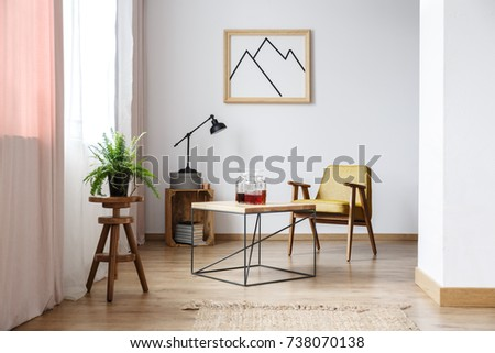 End table with three decanters with liquor, a mustard armchair and a picture on the wall above