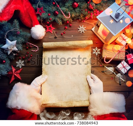 Santa Claus Desk Reading Wish List With Ornament And Christmas Gift  Royalty-Free Stock Photo #738084943