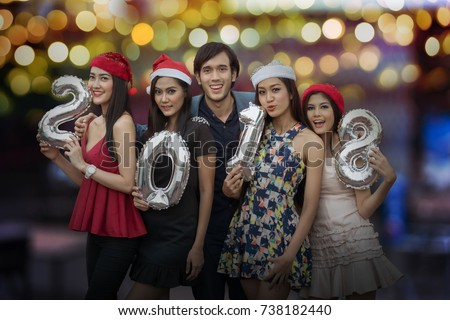 Cheerful young people holding cardboard number in night party, New Year's Party 2018 concept. #738182440