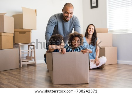 Happy african american father playing with children sitting in carton box at new home. Happy multiethinc family enjoying new home. Young parents and sons having fun during moving house. #738242371