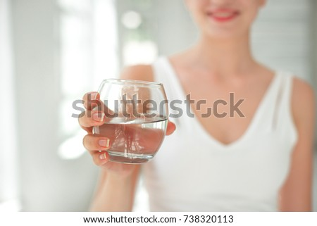 Female handa holding a clear glass of water. Slime body on background. #738320113
