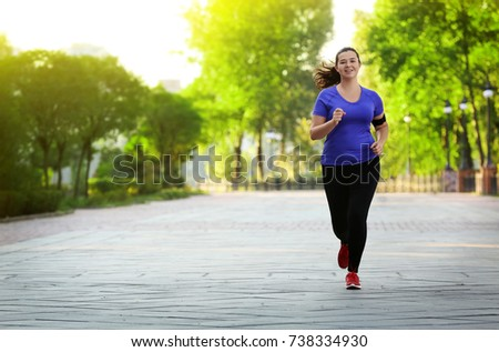 Overweight young woman jogging in park. Weight loss concept #738334930