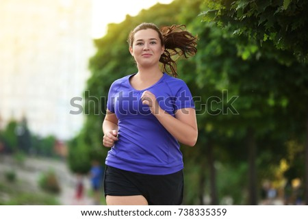 Overweight young woman jogging in the street. Weight loss concept #738335359
