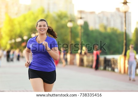 Overweight young woman jogging in the street. Weight loss concept #738335416