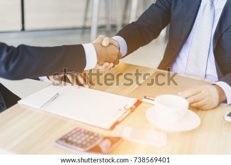 Investors reassure businessman or foreign partners in real estate investment new project. Lawyers join hands with clients to agree on the job with confidence while checking documents at coffee shop. #738569401