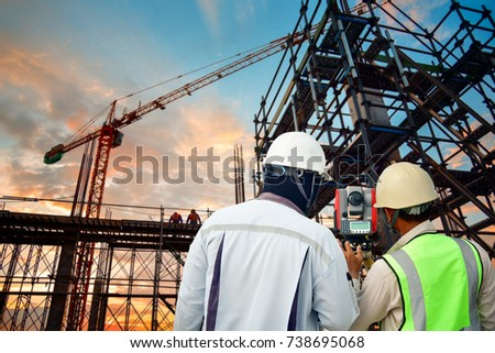 Surveyor builder Engineer with theodolite transit equipment at construction site outdoors during surveying work #738695068