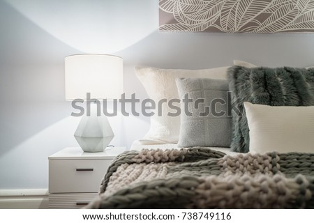 Modern home interior with bedroom setting including bedside table with lamp. Royalty-Free Stock Photo #738749116