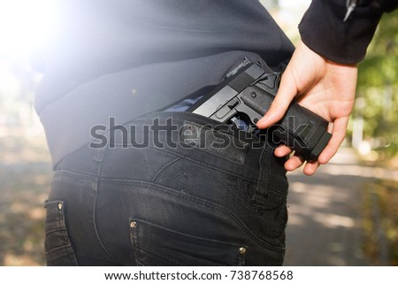girl pulls gun out of back pocket of jeans #738768568