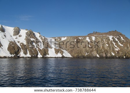 High sea rocks in snow against the sky and water #738788644
