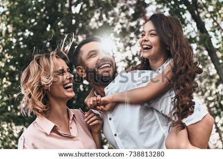 Family bonds. Happy young family of three smiling while spending free time outdoors #738813280