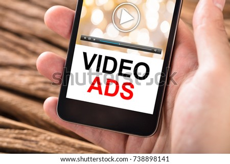 Close-up Of Person's Hand Holding Mobile Phone With Text Video Ads On Screen #738898141