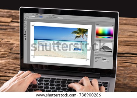 Close-up Of Person Editing Photo On Laptop At Desk