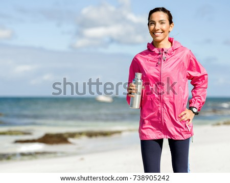 Beautiful girl in sport clothes drinking water after workout on the beach #738905242