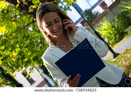Happy businesswoman talking on cell phone while reading reports in nature. #738934825