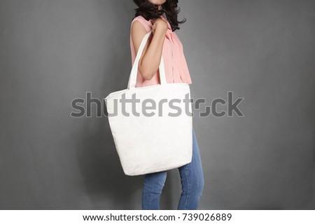 Girl is holding blank canvas tote bag, design mockup. Handmade shopping tote bag for girls. #739026889