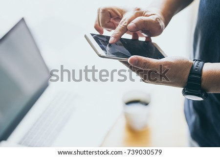 Smartphone in young man hand with blur laptop and coffee background . #739030579