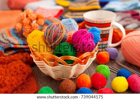 Balls of yarn for knitting. Balls of yarn for knitting in a wicker basket. A cup of tea, a knitting yarn, knitted clothes create coziness. Colorful multi-colored yarn for knitting. #739044175
